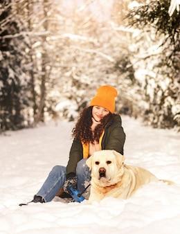 Linda garota feliz com um cachorro labrador no inverno na floresta em um dia ensolarado. amizade humano-animal
