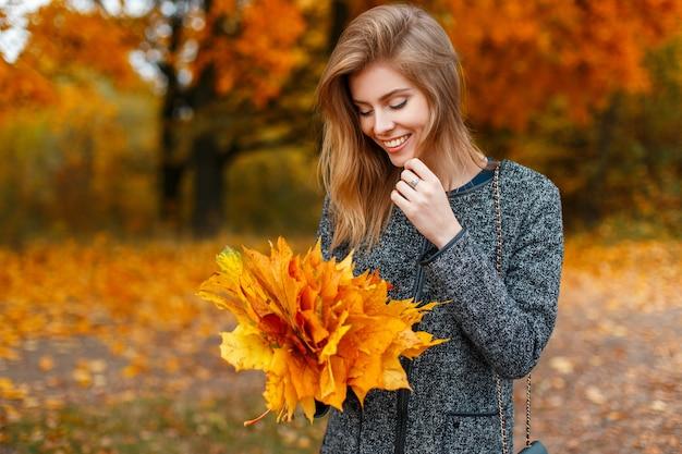 Linda garota feliz com um sorriso segurando um buquê de folhas amarelas em um parque de outono
