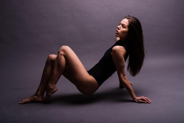 Linda garota feliz dançando e comemorando em pé de corpo inteiro, isolado no fundo do estúdio