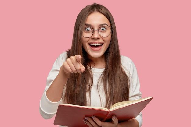 Linda garota feliz e surpresa sorri amplamente e aponta diretamente para a câmera