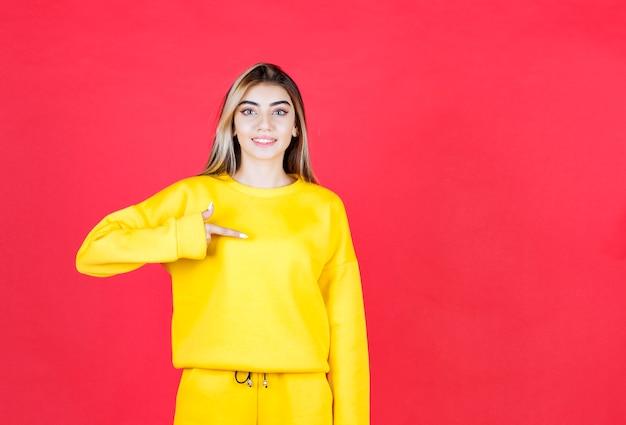 Linda garota feliz em pé e apontando algo na parede vermelha