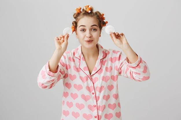 Linda garota feliz em pijamas e rolos de cabelo limpando a maquiagem com almofadas de algodão