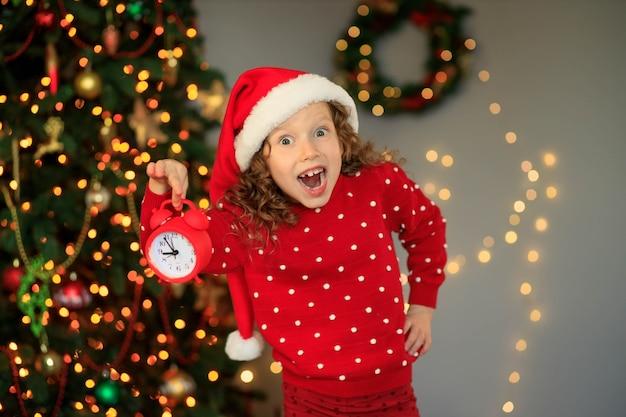 Linda garota feliz esperando o ano novo com um relógio de áudio nas mãos