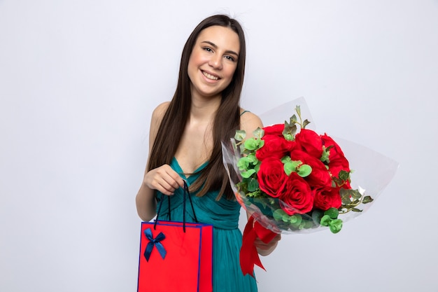 Linda garota feliz, inclinando a cabeça, segurando o buquê com uma sacola de presente