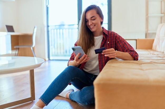 Linda garota feliz moderna casual usando smartphone e cartão de crédito para fazer compras online, pagar e encomendar produtos pela internet