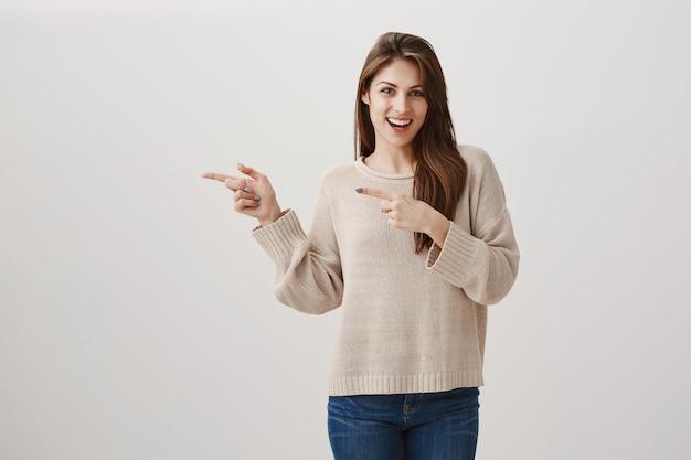 Linda garota feliz mostrando a promoção, apontando o dedo para a esquerda e sorrindo