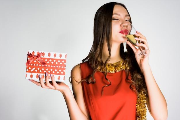 Linda garota feliz no vestido vermelho comemora o ano novo 2018, bebe champanhe e segura um presente