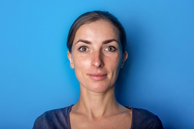 Linda garota feliz parece de orelhas após otoplastia em um fundo azul. otoplastia, cirurgia.