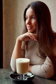 Linda garota feliz pensativa, sentado no café