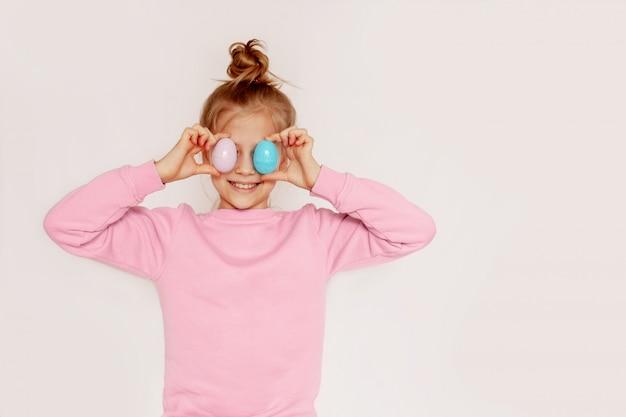 Linda garota feliz segurando um ovo de páscoa nas mãos dela