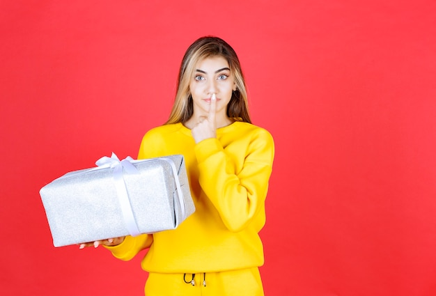 Linda garota feliz segurando uma caixa de presente na parede vermelha