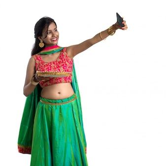 Linda garota feliz tirando uma selfie durante o festival da luz diwali