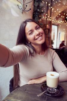 Linda garota feliz tomando uma selfie no café durante as férias de natal