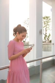 Linda garota feliz usando smartphone ao ar livre