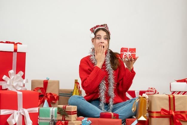 Linda garota festeira com chapéu de papai noel segurando um presente, colocando a mão na boca, sentada em volta dos presentes