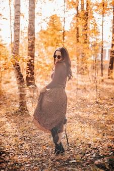Linda garota fica ao fundo na folhagem de outono no parque