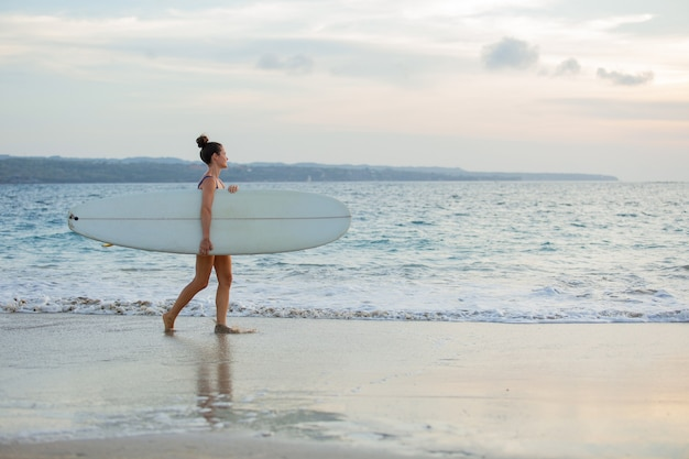 Linda garota fica na praia com uma prancha de surf.