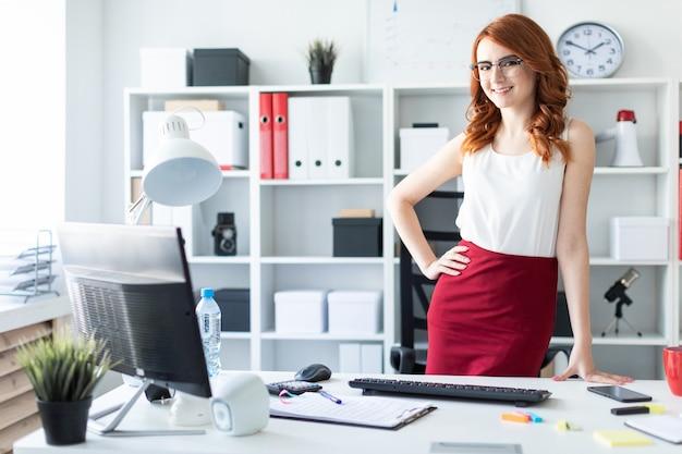 Linda garota fica no escritório perto da mesa