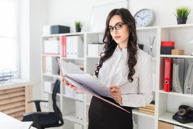 Linda garota fica no escritório polegares uma pasta com documentos.