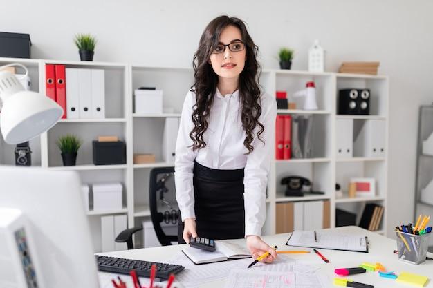 Linda garota fica perto da mesa de escritório e tem uma caneta e uma calculadora nas mãos dela.