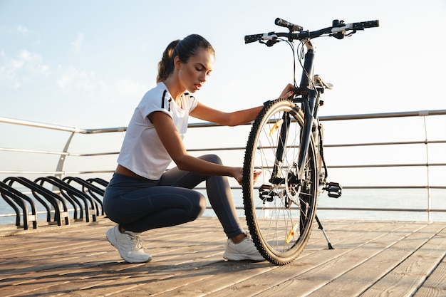 Linda garota fitness ao ar livre, consertando sua bicicleta, a paisagem do mar,