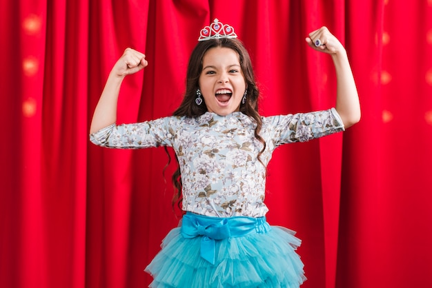 Linda garota, flexionando o músculo em pé na frente da cortina vermelha