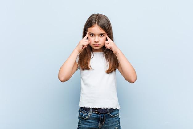 Linda garota focada em uma tarefa, mantendo-o dedos apontando a cabeça.