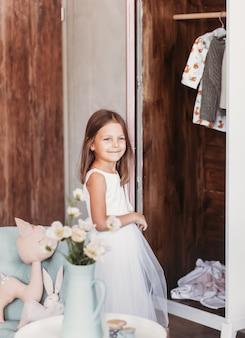 Linda garota fofa ao lado do armário aberto e sorri na sala iluminada