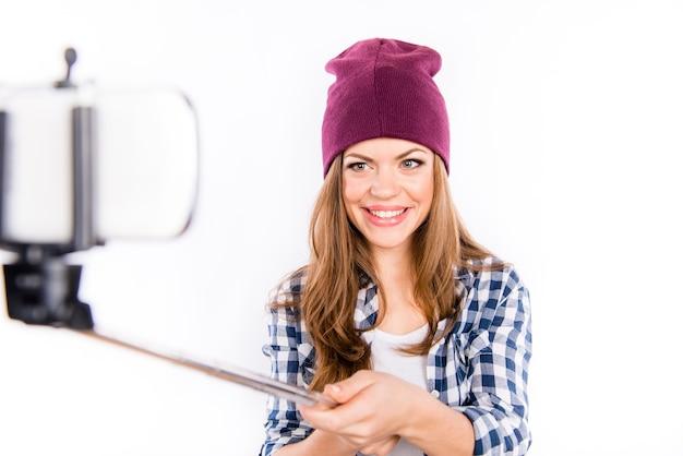 Linda garota fofa com um chapéu moderno tirando uma foto selfe no telefone
