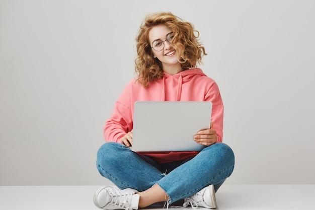 Linda garota freelance usando laptop, sentada no chão e sorrindo