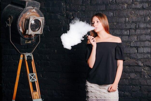 Linda garota fumando um cigarro eletrônico. vestida com roupas elegantes.