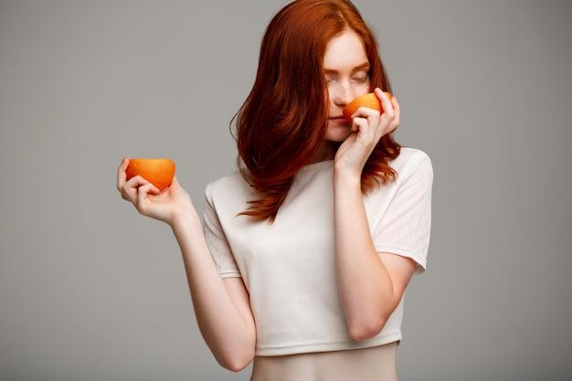 Linda garota gengibre segurando laranjas sobre parede cinza.