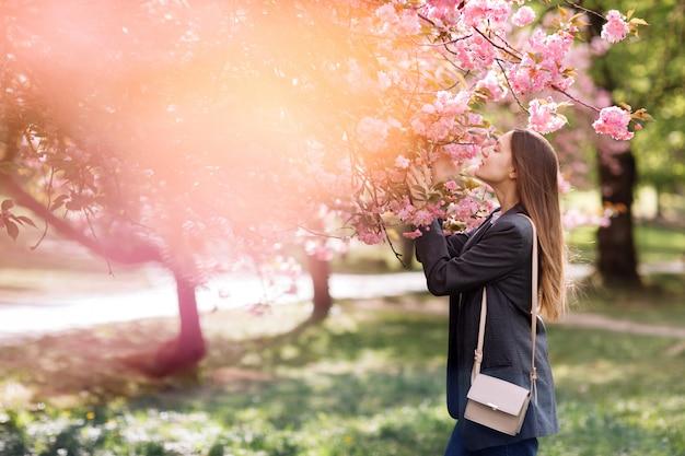 Linda garota gosta do perfume da árvore de florescência. retrato de uma mulher bonita com cerejeira desabrocham - garota inala o perfume das flores com os olhos fechados - conceito de primavera, natureza e beleza