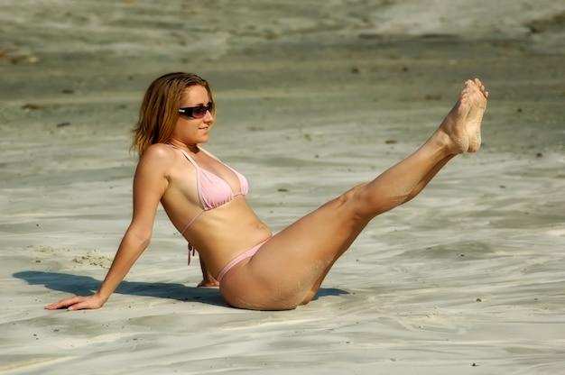 Linda garota gostosa em um maiô rosa senta-se em uma praia arenosa e aproveita o sol quente de verão durante as férias no mar. conceito de mulher jovem sensual