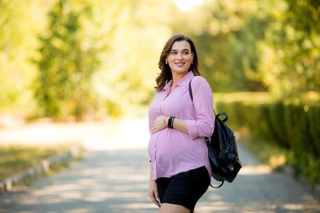 Linda garota grávida em uma caminhada de verão