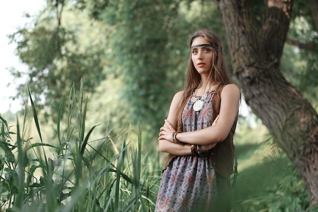 Linda garota hippie parada entre árvores na floresta