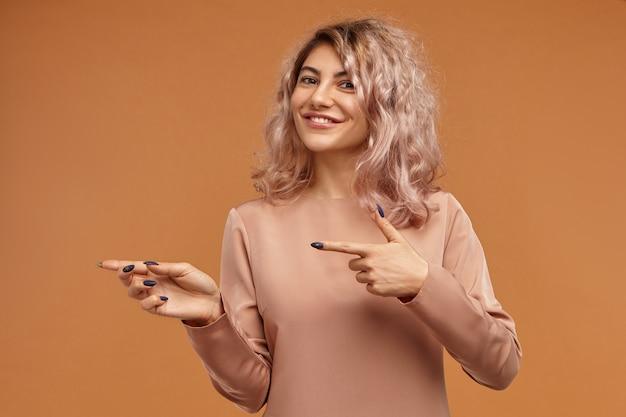 Linda garota hipster de aparência positiva e amigável com longas unhas pretas e cabelo rosado, sorrindo amplamente para a câmera e apontando o dedo indicador para o lado