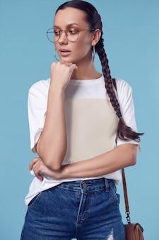 Linda garota hispânica encantadora em t-shirt branca, calça jeans e óculos