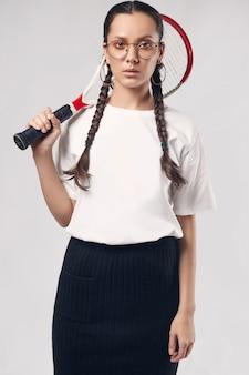 Linda garota hispânica encantadora em t-shirt branca com raquete de tênis