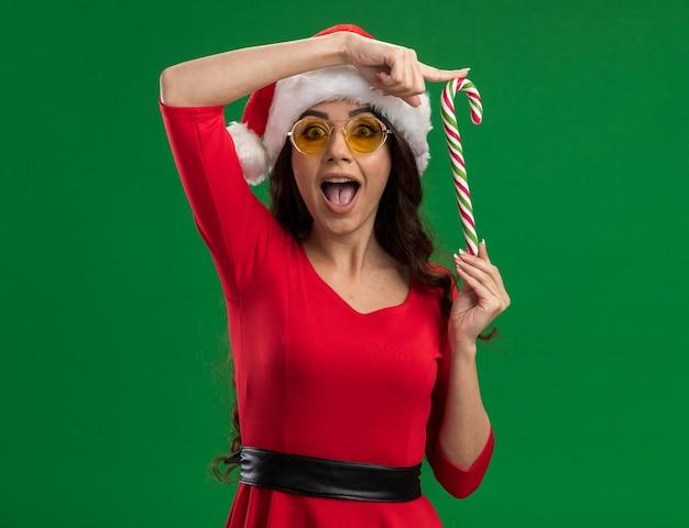 Linda garota impressionada com chapéu de papai noel e óculos segurando um bastão de doces de natal verticalmente, olhando para a câmera isolada sobre fundo verde