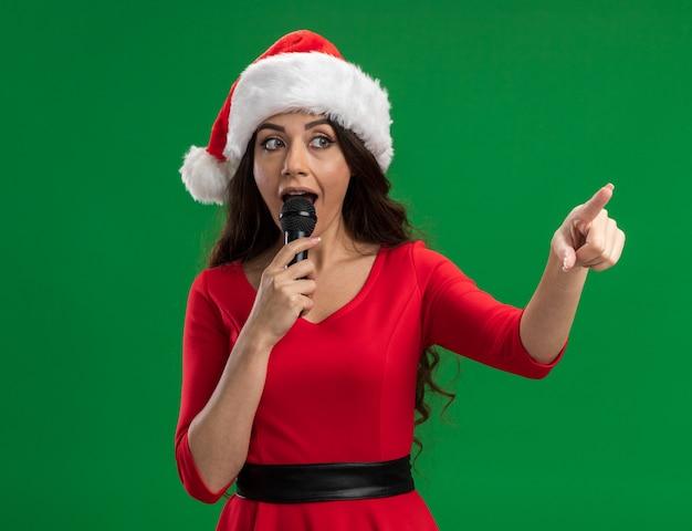 Linda garota impressionada com chapéu de papai noel falando no microfone, olhando e apontando para o lado isolado na parede verde