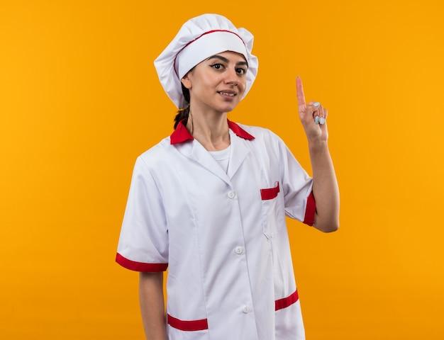 Linda garota impressionada com o uniforme de chef apontando para cima