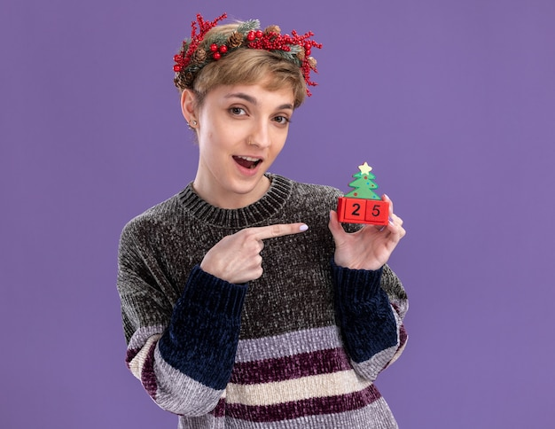 Linda garota impressionada com uma coroa de flores na cabeça e segurando um brinquedo da árvore de natal com a data apontando para ele olhando para a câmera isolada no fundo roxo
