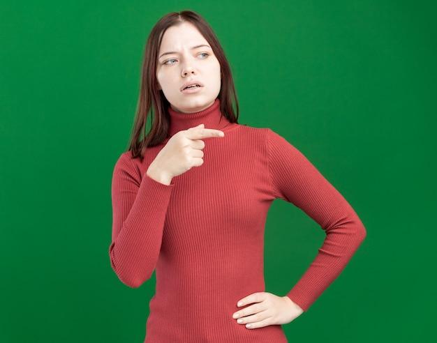 Linda garota impressionada mantendo a mão na cintura, olhando e apontando para o lado