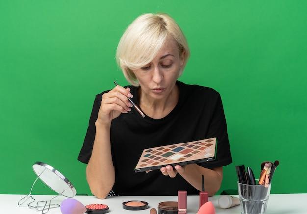 Linda garota impressionada se senta à mesa com ferramentas de maquiagem segurando e olhando para a paleta de sombra com pincel de maquiagem isolado na parede verde