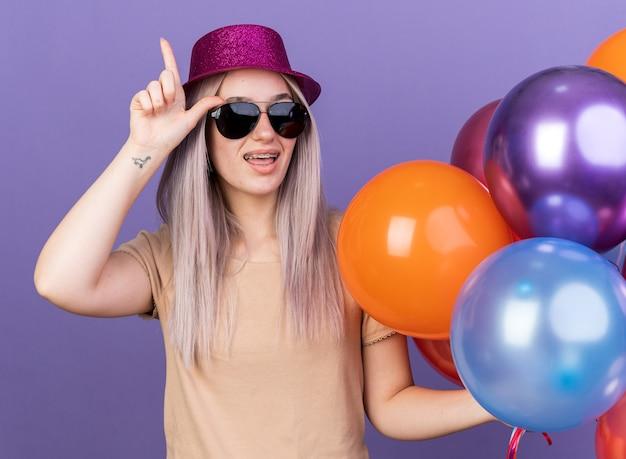 Linda garota impressionada usando aparelho dentário e chapéu de festa com óculos segurando balões com a sacola de presente apontando para cima isolada na parede azul