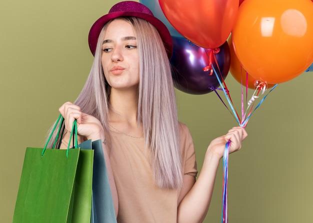 Linda garota impressionada usando chapéu de festa segurando balões e uma sacola de presente