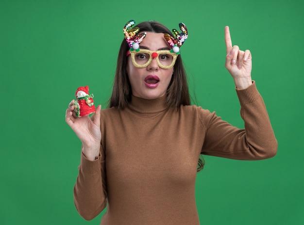 Linda garota impressionada, vestindo um suéter marrom e óculos de natal, segurando pontas de brinquedo de natal isoladas sobre fundo verde