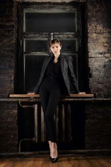 Linda garota, inclinando-se para peitoril da janela na sala com paredes de tijolo queimado e moldura da janela