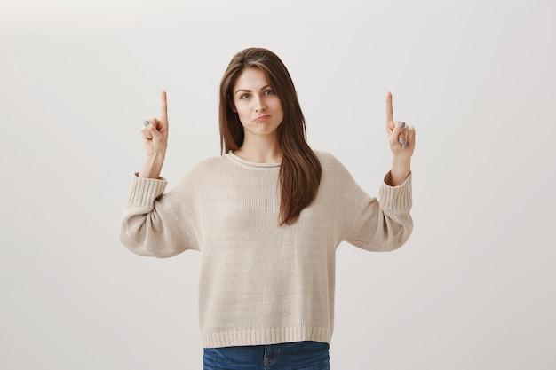 Linda garota indecisa apontando os dedos para cima e fazendo beicinho